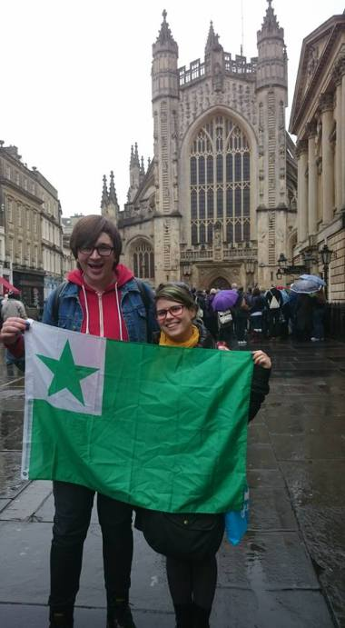 Two smiling women in front of Bath Abbey holding Esperanto flag