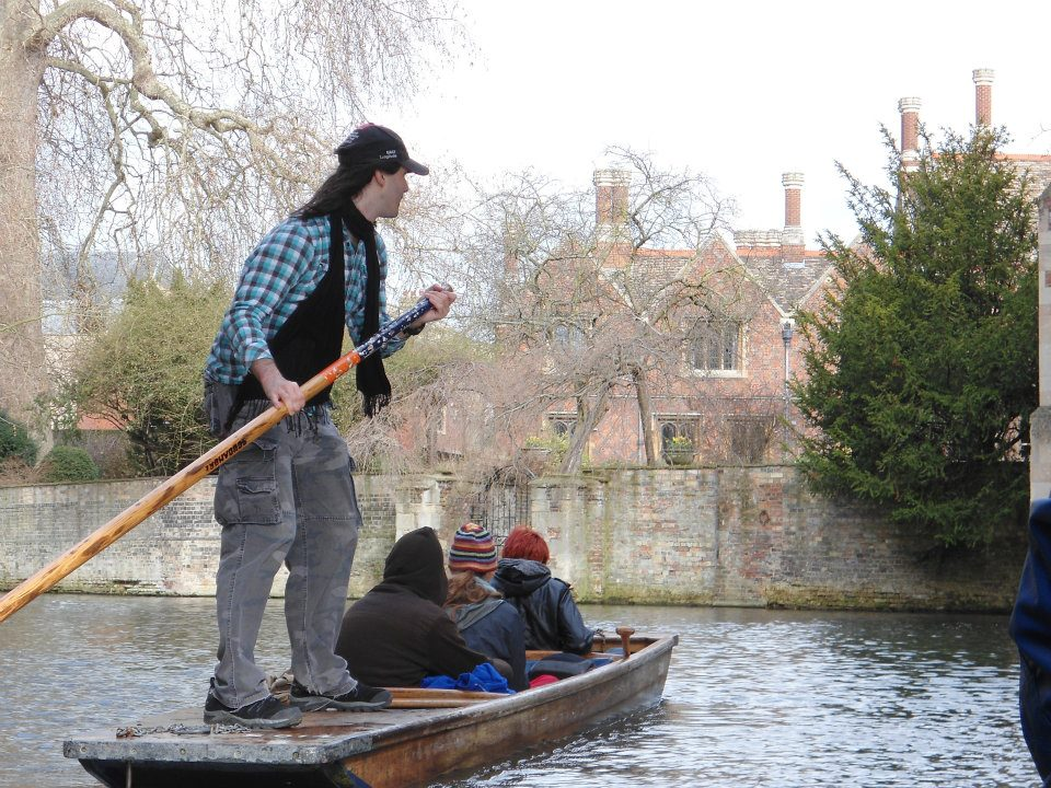 Four people punting on a boat in Cambridge
